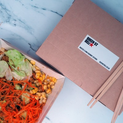 Rectanglar biodegradable paper stickers applied to deli box on a stone surface