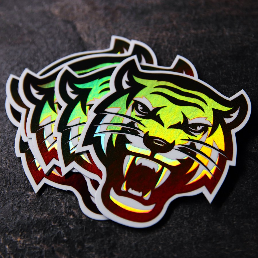 A small pile of holographic die ut tiger stickers on a table