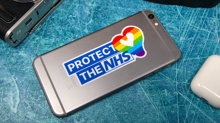 An iphone with a protect the NHS sticker applied on a blue background