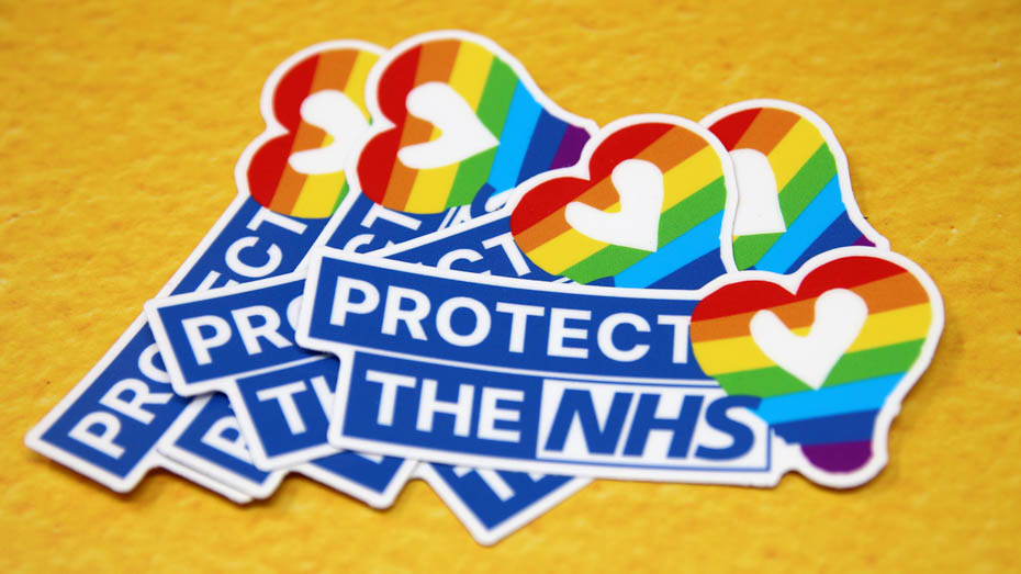 A pile of protect the NHS stickers on a yellow background