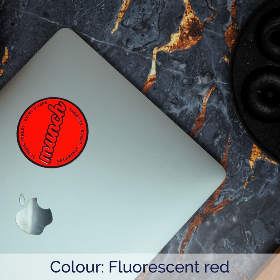 Fluorescent red circle sticker applied to a Macbook Pro