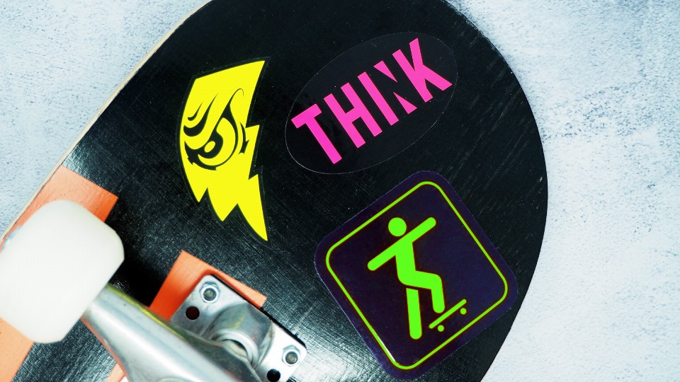 Fluorescent yellow, fluorescent pink & fluorescent green stickers on a skateboard
