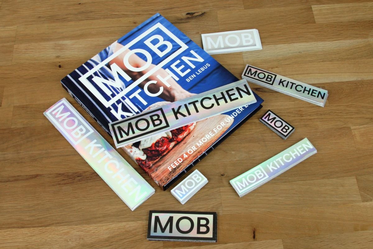 Several Mob Kitchen rectangle stickers and a cook book