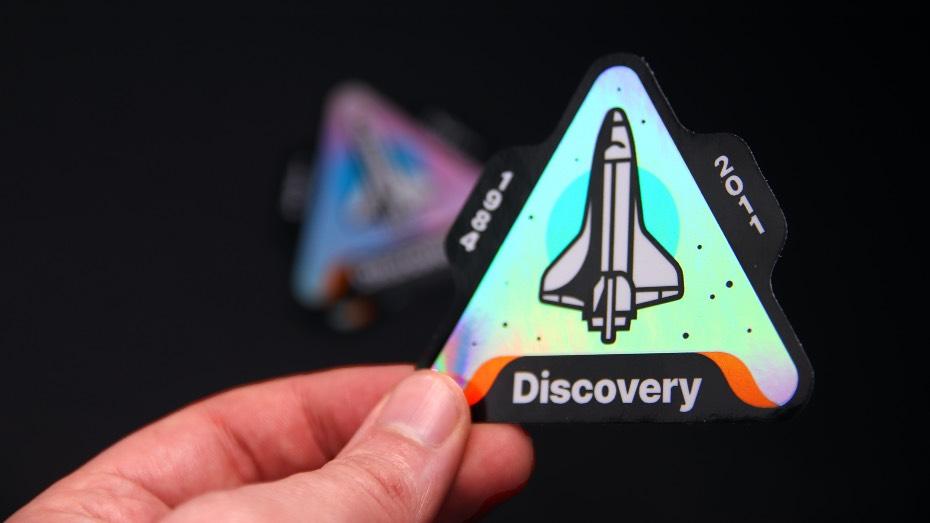 Holographic die cut sticker with a space rocket on it