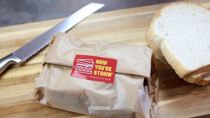 White eco-friendly compostable rounded corner stickers applied to sandwich wrapper packaging on a chopping board