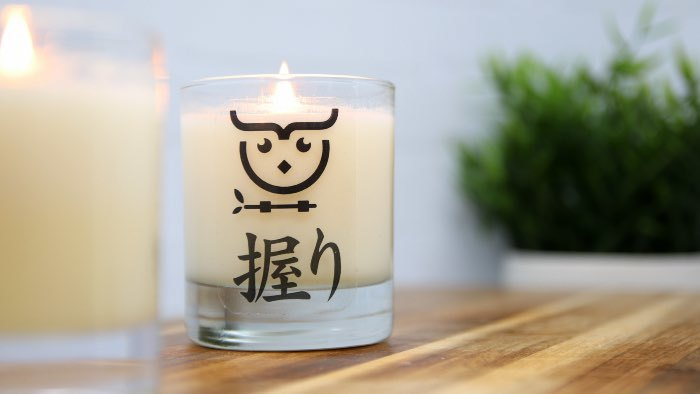 Clear eco-friendly compostable candle sticker applied to a glass candle jar