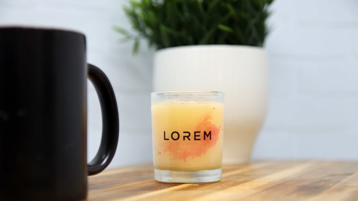 Clear eco-friendly compostable candle sticker applied to a glass candle jaron a shelf with a mug and a plant