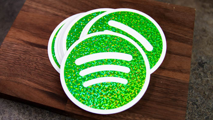 A pile of circular Spotify glitter stickers on a wooden block