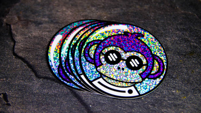A pile of circular space monkey glitter stickers on a kitchen counter