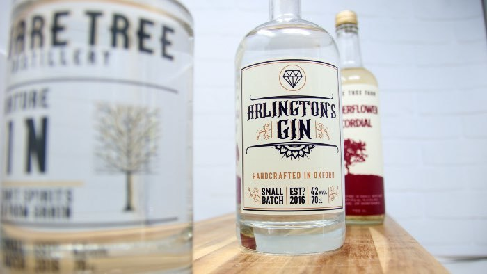 White eco-friendly compostable square stickers applied to gin bottles on a wooden shelf