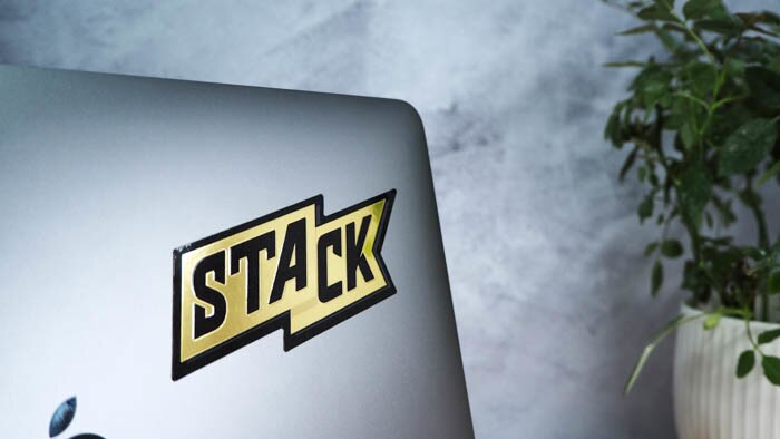 STACK mirror gold logo sticker on a space grey Apple MacBook with a green plant in the background