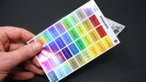 Sticker it colour swatch printed on holographic sticker material in a persons hand