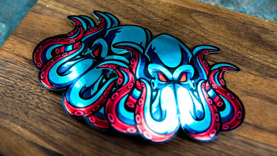 A pile of octopus die cut mirror silver stickers on a wooden block