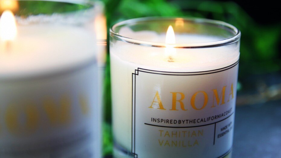 Clear sticker in a rectangle shape applied to a vanilla candle which is lit and in front of a green plant