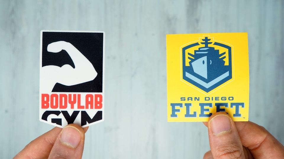 Bodylab die-cut sticker & a San Diego Fleet kiss-cut sticker both being held next to each other
