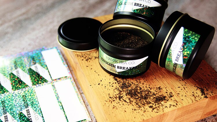 Glitter labels on sheets in full colour on black tins filled with loose leaf tea on a wooden block