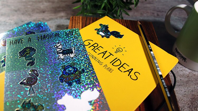 Glitter labels on sheets in full colour on a yellow notebook