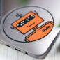 Orange robot clear vinyl circle sticker on a silver Macbook