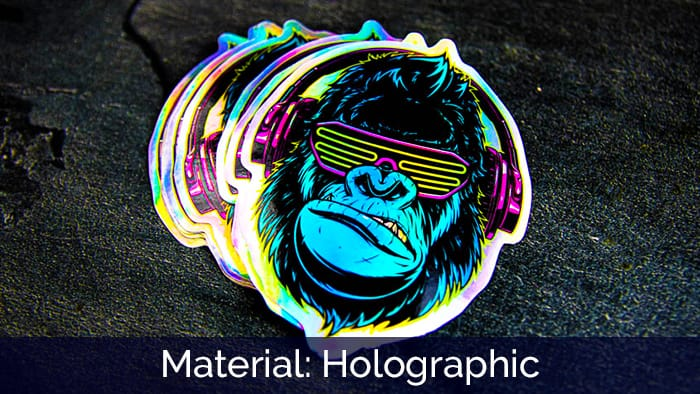 A pile of die-cut gorilla holographic stickers and a black surface