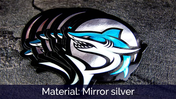 A stack of die-cut mirror silver shark gamer stickers on a dark table