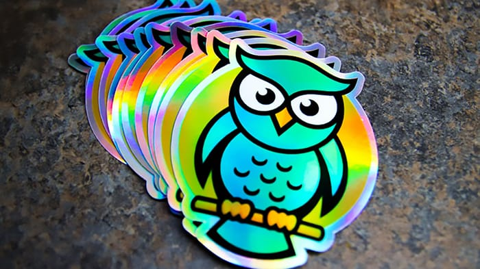 A stack of holographic die cut owl stickers fanned out on dark table