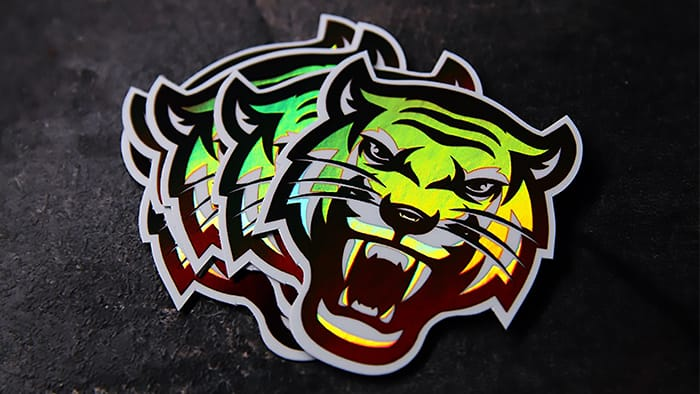 A stack of holographic die cut tiger stickers fanned out on dark table