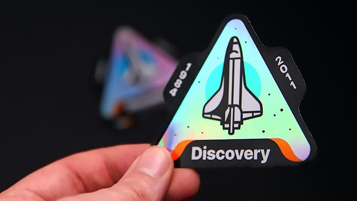 A custom die cut discover shuttle holographic sticker held in hand