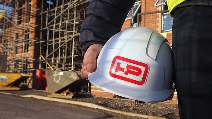 Rounded corner heavy duty hard hat sticker stuck onto a white hard hat on construction site