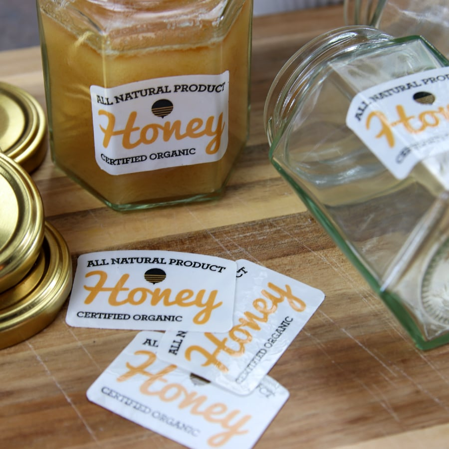 Eco-friendly stickers applied to honey jars on a wooden block