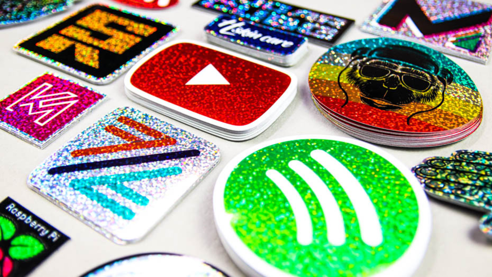 Many stacks of glitter stickers in all shapes on a white worktop