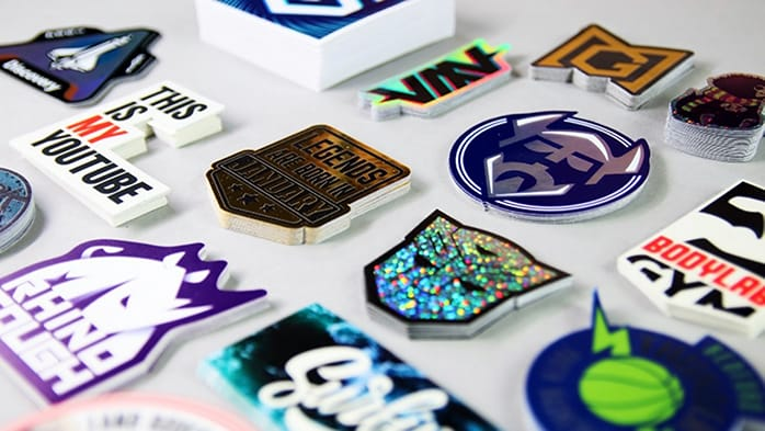 Various die cut custom printed stickers in piles on a white background